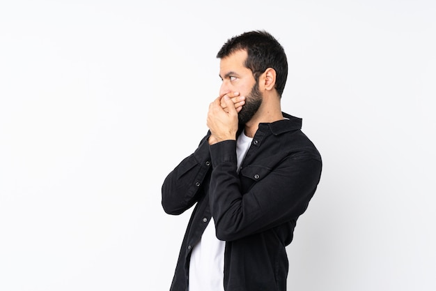 Young man with beard over isolated white covering mouth and looking to the side