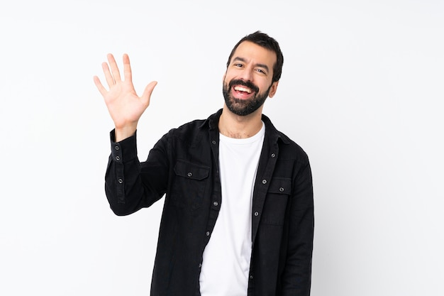 Young man with beard over isolated white saluting with hand with happy expression