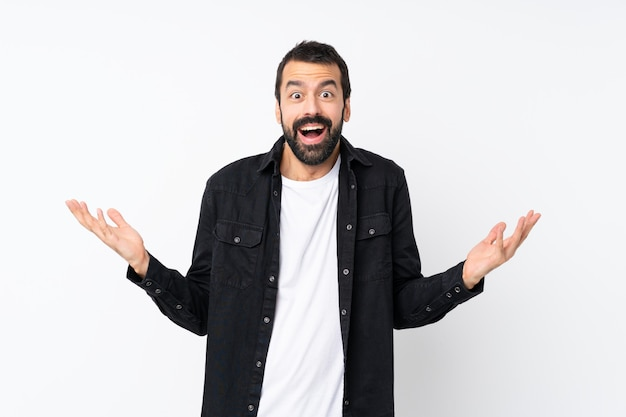Young man with beard over isolated white wall with shocked facial expression