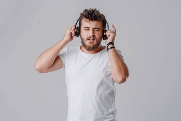 A young man with a beard listens to loud music in wireless headphones