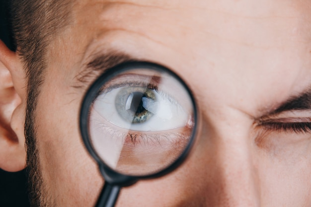 A young man with a beard looks through a magnifying glass.