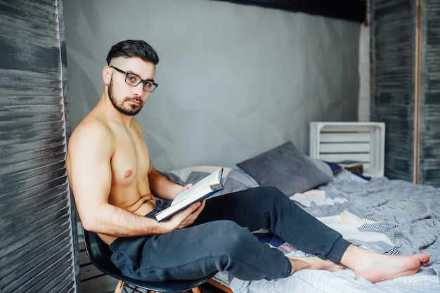 Young man with beard lying on bad at morning time and holding book on his hands.