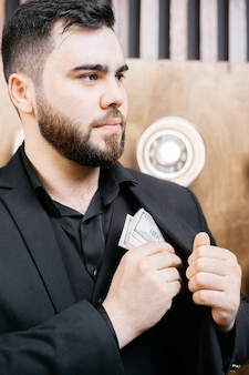 Young man with beard putting dollars money in his pocket