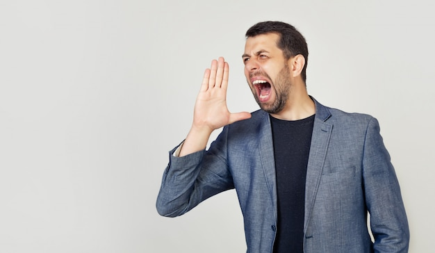 A young man with a beard screams out loud with his hand near his mouth