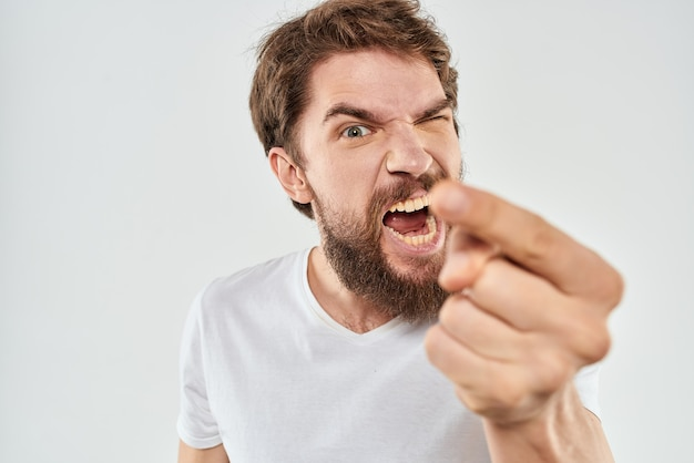 A young man with a beard in a t-shirt angry