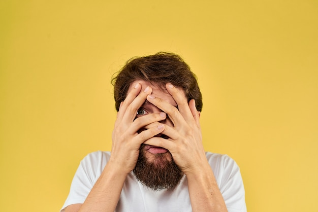 A young man with a beard in a t-shirt shows different emotions, fun, sadness, anger  on the space