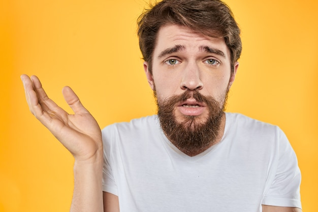 Young man with a beard in a t-shirt shows different emotions, fun, sadness