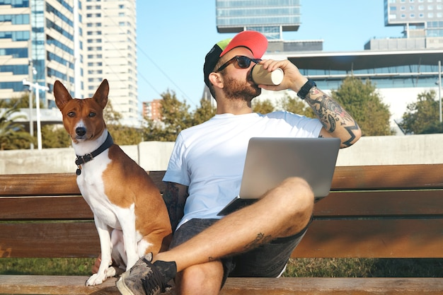 A young man with beard and tattoos and a laptop on his knees is drinking coffee from a paper cup and his dog sits next to him