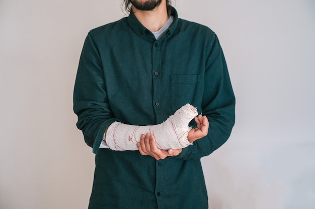 Young man with beard and tshirt holding a bandaged arm