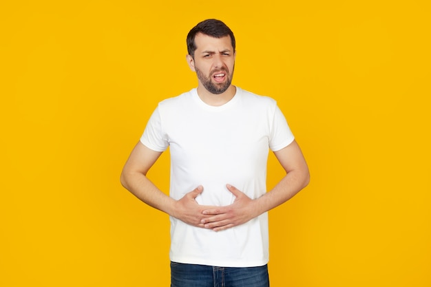Young man with a beard in a white t-shirt with a hand on his stomach because of indigestion, feeling sick.