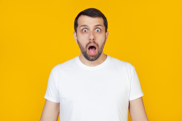 Young man with beard in white t-shirt with open mouth, afraid and shocked by unexpected expression