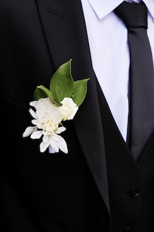 Young man with a beautiful boutonniere of white roses or chrysanthemums and green leaves, on the lapel of his jacket. the groom in a white shirt, tie, black or dark blue suit. wedding theme.