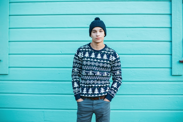 Young man with a beautiful smile in a knitted hat with blue eyes in a blue christmas vintage sweater in jeans stands in the city near a bright blue wooden house. charming guy.