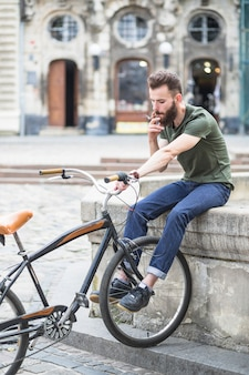Young man with bicycle smoking cigarette