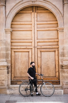 Young man with bicycle standing near the closed vintage door