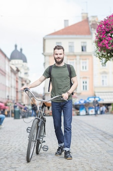 Young man with bicycle walking on street