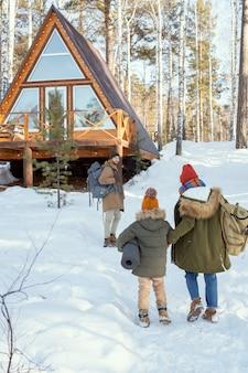 森の中のカントリーハウスのそばに立って、彼に向かって移動している彼の妻と娘を見ている大きなリュックサックを持つ若い男