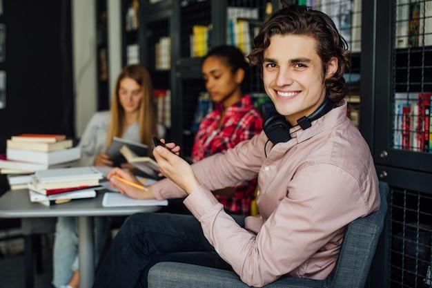 Молодой человек с черными волосами читает книгу и подростки в повседневной одежде в библиотеке