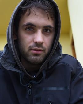 黒のパーカーと短いひげを持つ若者