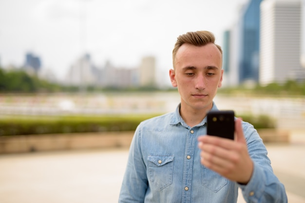 Young man with blond hair using mobile phone in park