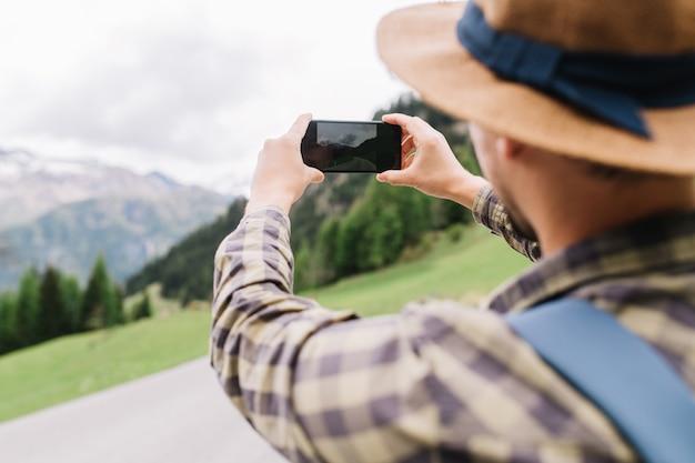 青いバックパックを持つ若い男は、山に行く風景の写真を撮ります