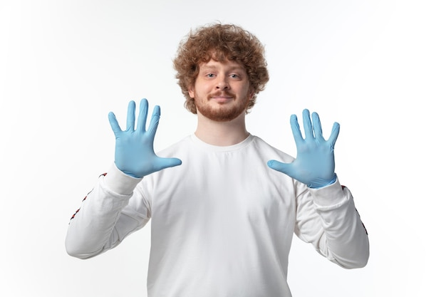 Young man with blue gloves on white wall