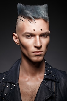 Young man with blue hair and creative makeup and hair.