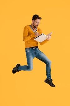Молодой человек с книгой прыгает