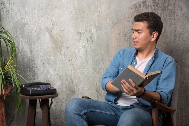 電話で見て、大理石の背景の椅子に座っている本を持つ若い男。高品質の写真