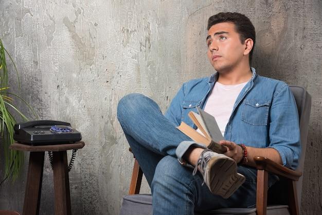 大理石の背景に椅子に座って見上げる本を持つ若い男。高品質の写真