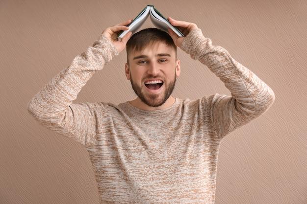 色の表面に本を持つ若い男