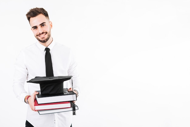 Young man with books and mortarboard