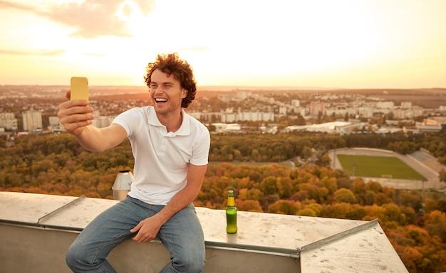 옥상에 맥주 병을 가진 젊은 남자