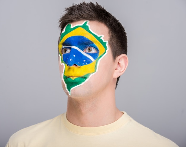 Young man with brazilian flag painted on his face.