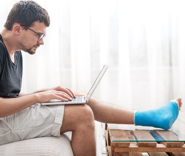 Young man with a broken leg in blue splint for treatment of injurie and ankle sprain is using a laptop at home.