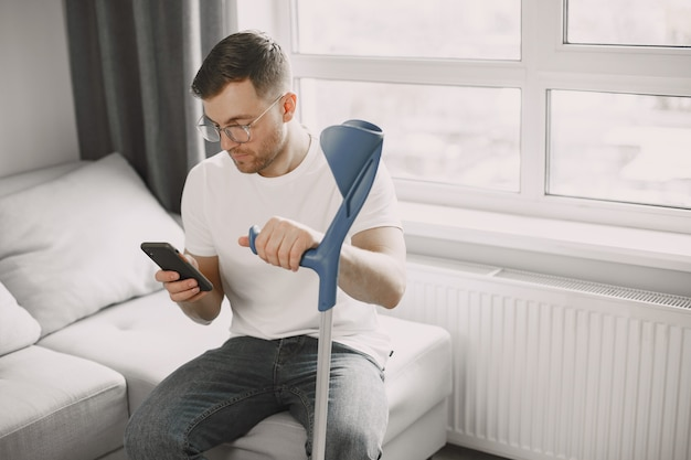 Young man with broken leg at home. using smartphone.