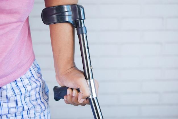 Молодой человек со сломанной ногой на костылях