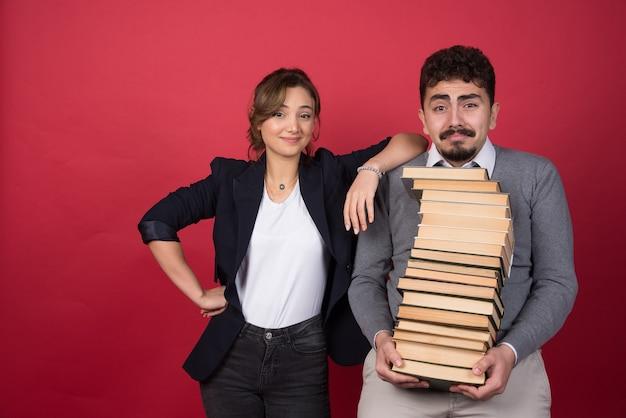 Giovane con un mazzo di libri e collega di donna in piedi sulla parete rossa