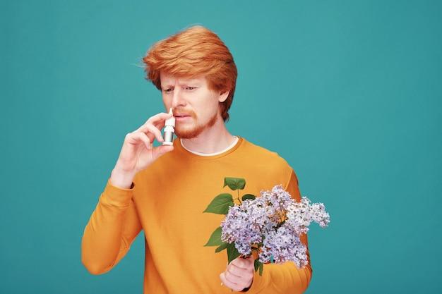 Молодой человек с букетом ароматной сирени использует спрей для носа, чтобы вылечить аллергическую реакцию на сезонное цветение, стоя в изоляции