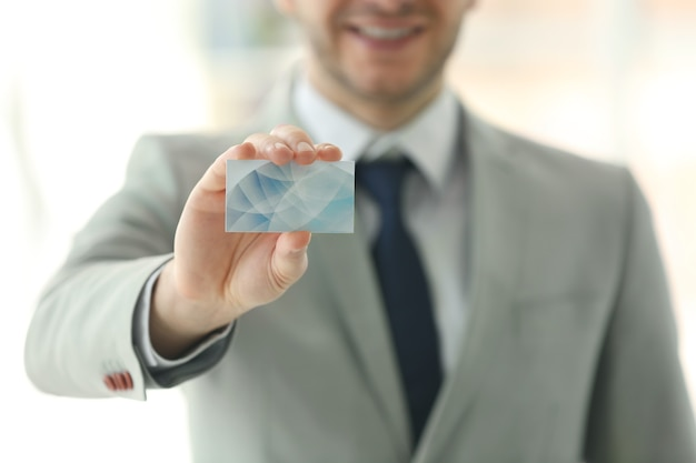 Young man with business card on white
