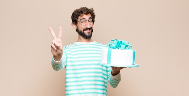 Young man with a cake against flat wall