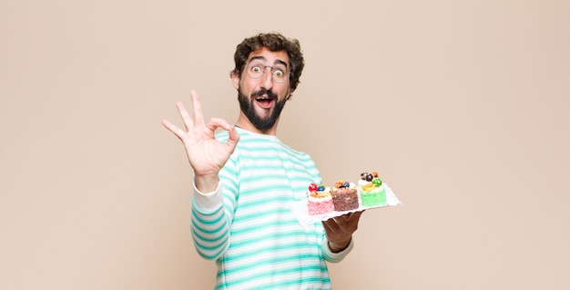 Young man with a cake on wall