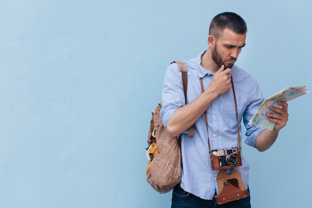 Young man with camera around his neck reading map on blue backdrop