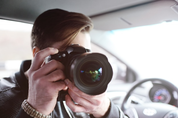 Young man with a camera in the car