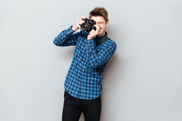 Молодой человек с фотоаппаратом делает фото