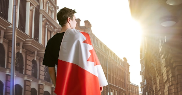 A young man with a canada national flag on the soulders patriotism and proud feelings
