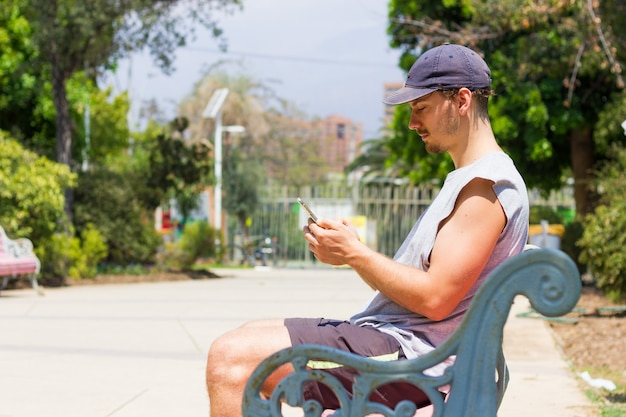 화창한 날 공원 벤치에 앉아 핸드폰을 들고 모자를 쓴 젊은 남자