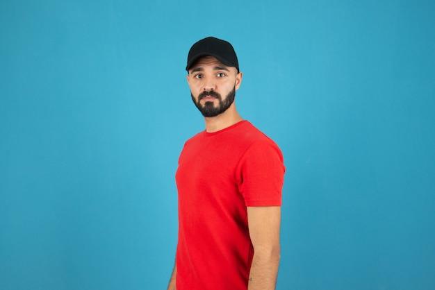 立ってポーズをとって赤いtシャツを着て帽子をかぶった若い男。