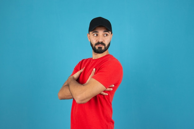 Young man with cap wearing red t-shirt standing with crossed arms .