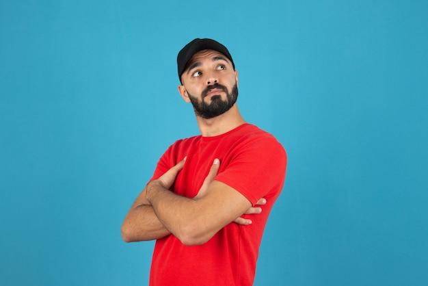 腕を組んで立っている赤いtシャツを着て帽子をかぶった若い男。